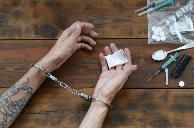 Drug traffickers were arrested along with their heroin. police arrest drug dealer with handcuffs Premium Photo