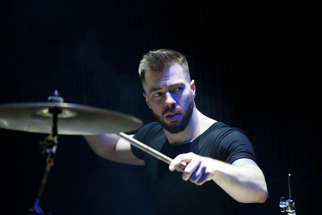 Drummer in a cap and headphones plays drums at a concert Premium Photo