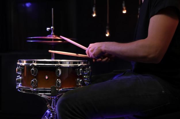 Барабанщик играет на малом барабане в темноте. концепция концерта и живого выступления. Бесплатные Фотографии