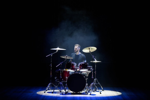 Drummer playing the drums with smoke and powder Premium Photo