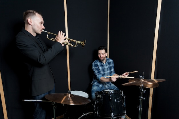 Drummer and trumpet player performing Free Photo
