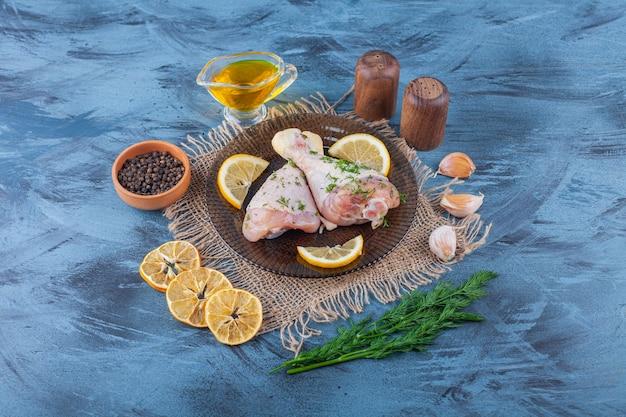 파란색 표면에 삼베 냅킨에 말린 레몬, 양념 그릇, 딜 및 기름 옆 유리 접시에 나지만과 레몬 무료 사진