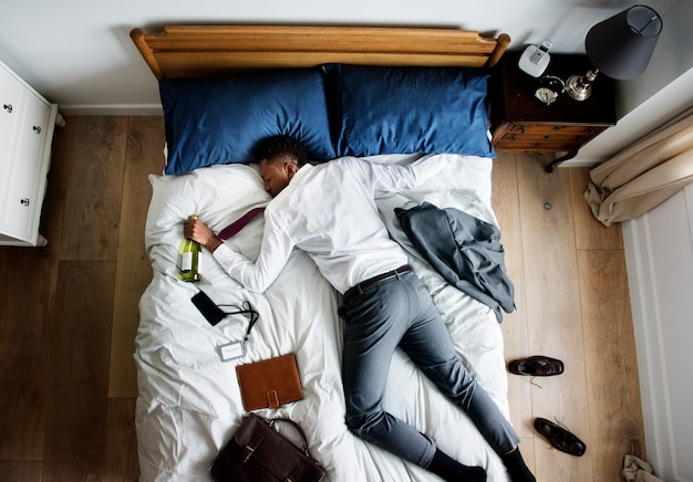 Drunk african american business man falling asleep as soon as he came back home Premium Photo