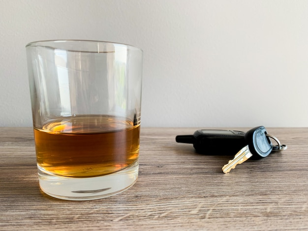 Drunk driving concept. glass with whiskey and key on the table. Premium Photo