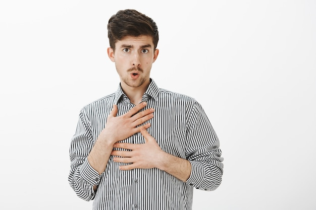 Drunk funny caucasian male coworker in striped shirt, making fun of silly coworker, folding lips and touching himself, holding hands on chest, being playful and unfocused over gray wall Free Photo
