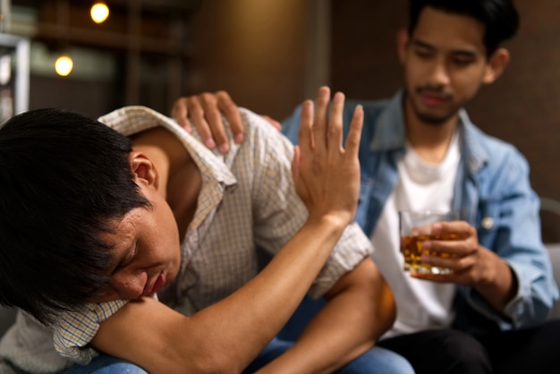 Drunk man sitting on sofa refusing whiskey from his friend by raising his hand to stop. Premium Photo