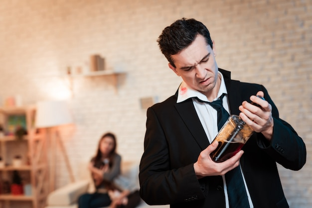Drunk man in suit drinks alcohol at home Premium Photo