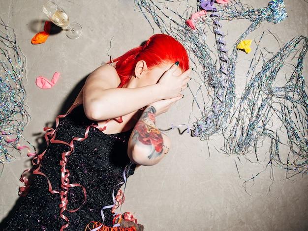 바닥에 손으로 얼굴을 덮고 취한 여자 프리미엄 사진