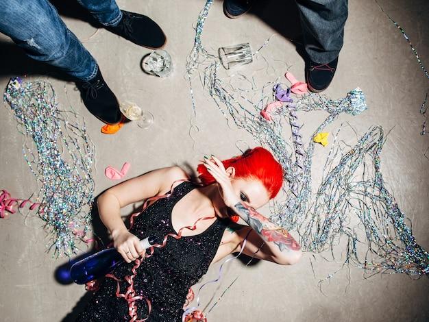 파티 후 병 바닥에 누워 취한 여자 프리미엄 사진