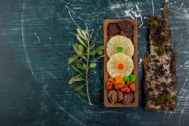 青いテーブルの上の木片とドライとゼリーのフルーツボード 無料写真