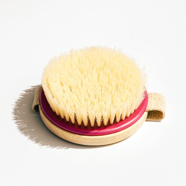 Dry body massage brush on white wall at sunny day. tool for smooth and soft skin. Premium Photo