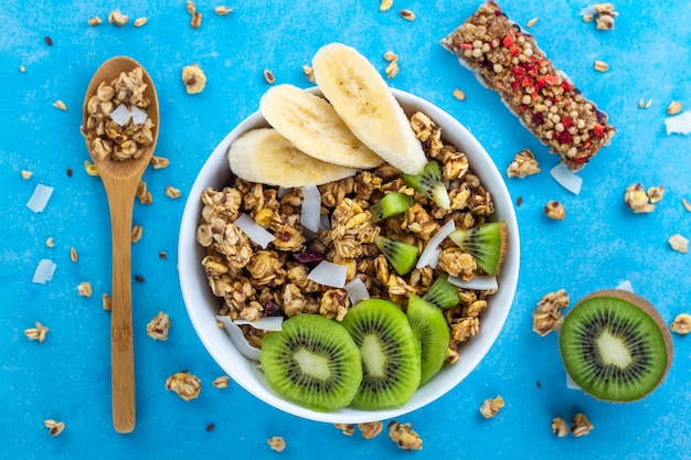 Dry breakfast cereals. crunchy honey muesli bowl with slices of fresh banana and kiwi on a blue background. healthy, fitness and fiber food. top view. breakfast time Premium Photo