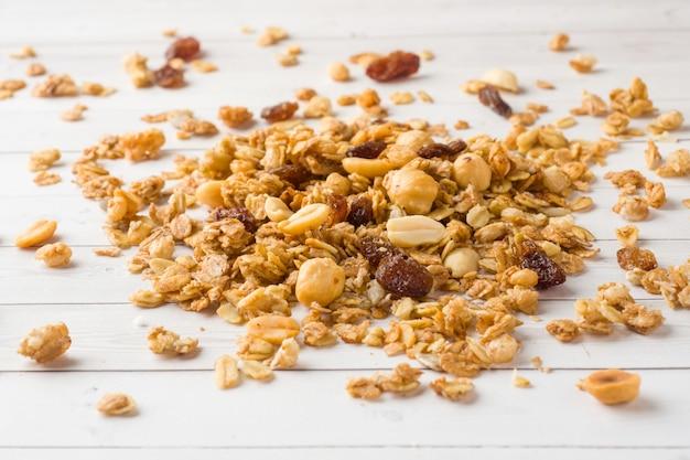 Dry breakfast of oat flakes on white table Premium Photo
