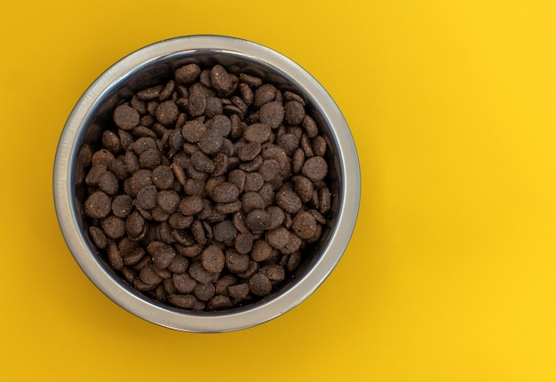Dry brown pet food for cats or dogs in a metal bowl on a yellow Premium Photo