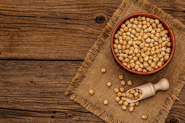 Dry chickpea in ceramic bowl on old wooden table. traditional ingredient for cooking hummus Premium Photo