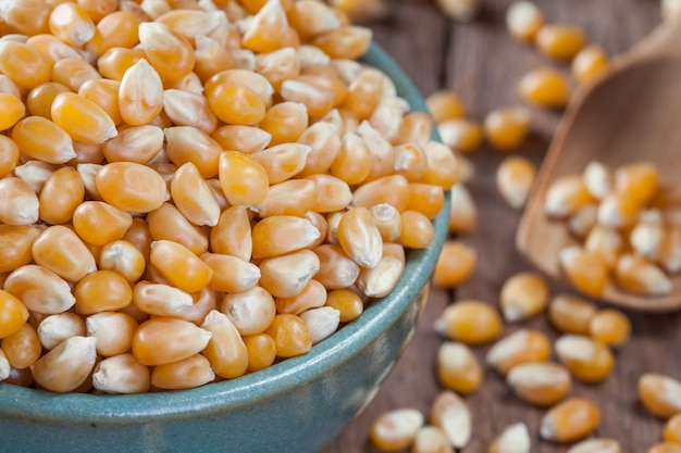 Dry corn kernels in a green bowl, set on a wooden table. Premium Photo