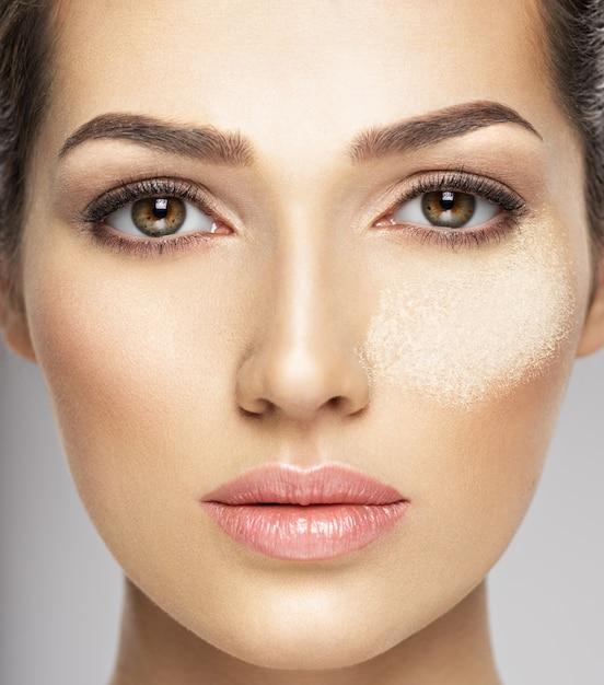 ドライコスメティックメイクアップパウダーが女性の顔にあります。美容トリートメントのコンセプト。女の子は化粧をします。 無料写真
