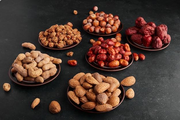 Сухие финики и орехи в блюдце на черной поверхности. Бесплатные Фотографии