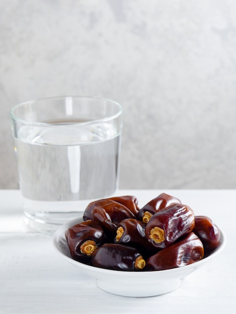 Dry dates and a glass of water on white table - ramadan, iftar food. Premium Photo