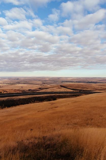 Сухая пустынная местность с дорогой посередине и удивительными облаками в небе Бесплатные Фотографии