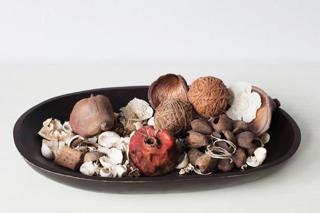 乾燥した花、葉、白いテーブルに木製の皿の上の果物 Premium写真