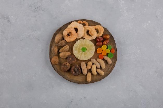 中央の木製大皿にドライフルーツとスナック 無料写真