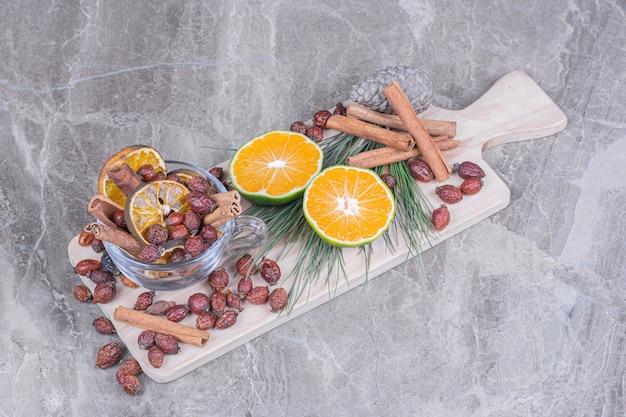 Fianchi asciutti e fette d'arancia con arance fresche su tavola di legno. Foto Gratuite