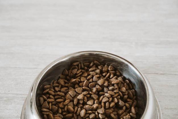 Dry kibble dog food in bowl on the floor Premium Photo