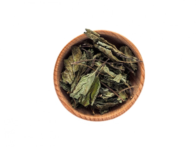 Dry leaves of melissa officinalis in a wooden cup on a white table. Premium Photo