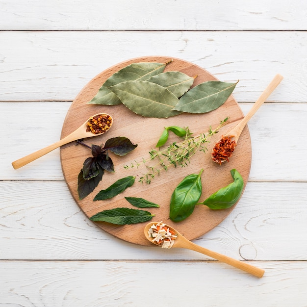 Dry leaves and spices on round wooden tray Free Photo