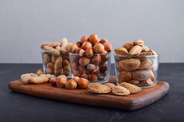 Dry nuts in glass cups on a wooden platter. Free Photo