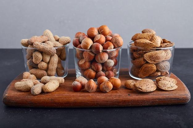 Сухие орехи в стеклянных чашках на деревянном блюде на синем фоне. Бесплатные Фотографии