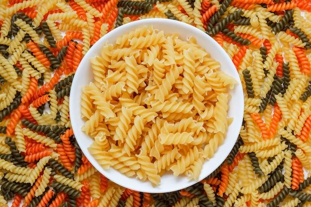 マカロニテーブルの白い皿にパスタを乾燥させ、平らに置きます。 無料写真