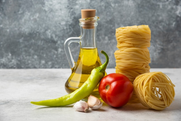 Dry pasta nests, bottle of olive oil and vegetables on white table. Free Photo