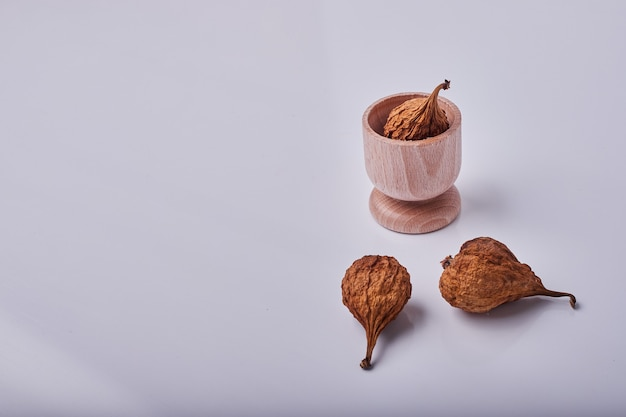 木製のカップと灰色の背景に梨を乾燥します。 無料写真