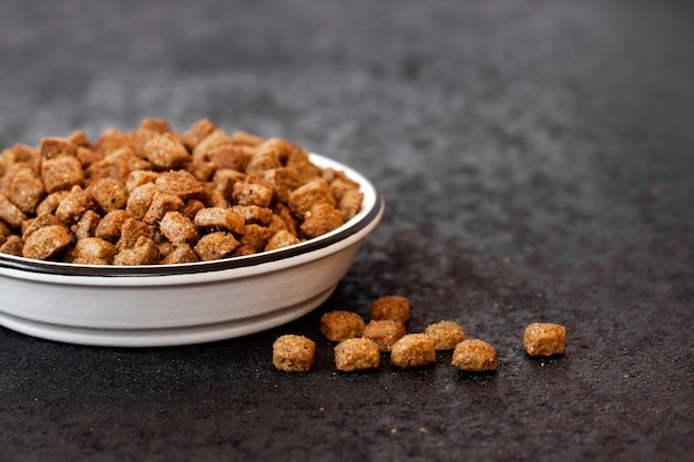 Dry pet food in a white ceramic bowl on black background with copy space Premium Photo
