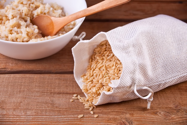 Dry rice in a bag and cooked brown rice in white bowl on the wooden background. Premium Photo