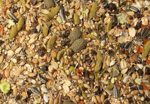 マウス、ウサギまたはデグートップビューの齧歯類食品テクスチャ背景を乾燥します。シリアル、種子、エンドウ豆、乾燥野菜のバランスの取れたハムスターの飼料パターン Premium写真