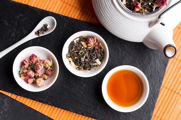 Сухие розы и чайная трава с чайником на черном сланце по столовому Бесплатные Фотографии