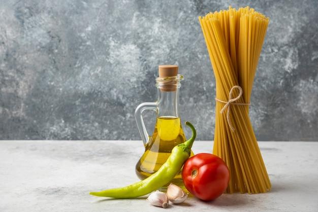 白いテーブルの上に乾いたスパゲッティ、オリーブオイルと野菜のボトル。 無料写真
