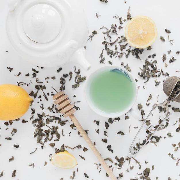 Dry tea leaves; tea strainer; lemon; fresh green tea; and teapot on white backdrop Free Photo