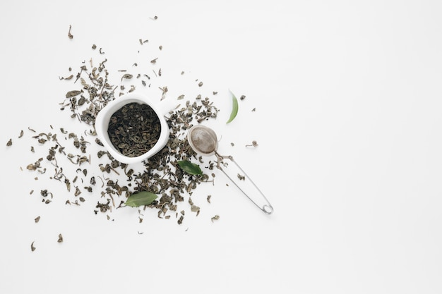 Dry tea leaves with coffee leaves and tea strainer on white backdrop Free Photo