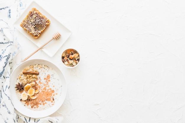 オーツの健康的な朝食とdryfruitsのオーバーヘッドビューは、テクスチャの白い背景に 無料写真