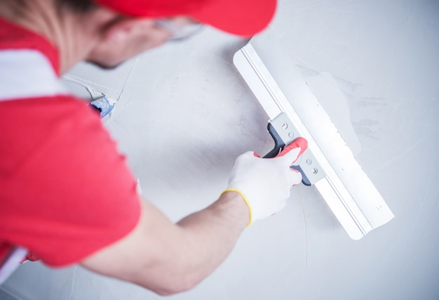 Drywall patch by worker Free Photo