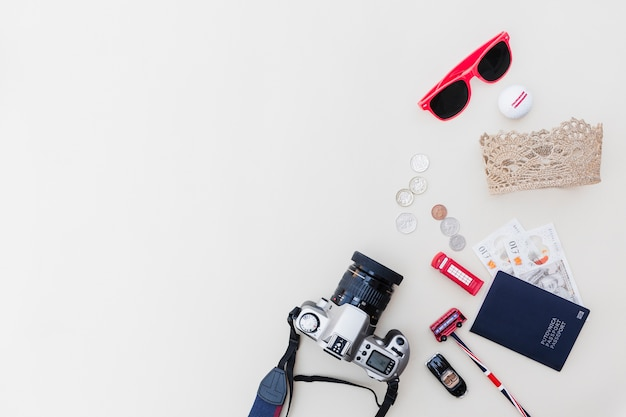 Dslr camera, passport, currencies, sunglasses and toys on bright backdrop Free Photo