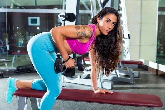 ダンベル上腕三頭筋キックバック女の子運動ジムで Premium写真