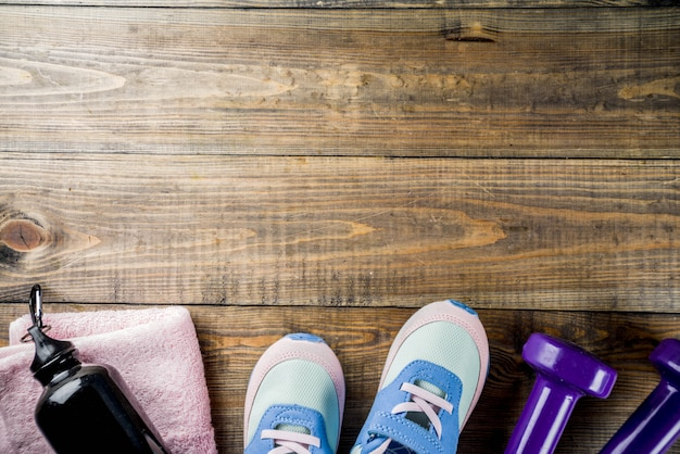 Dumbbells, sneakers, a towel and a bottle of water on wooden background Premium Photo