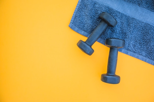 Dumbbells on towel over yellow background Free Photo