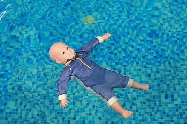 Dummy drowning training baby doll float in the pool. Premium Photo