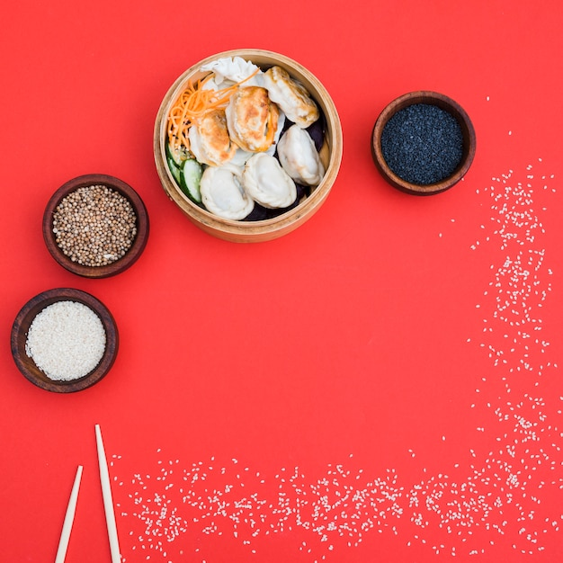 Dumplings in steamer with coriander seeds; black and white sesame seeds bowl on red backdrop Free Photo
